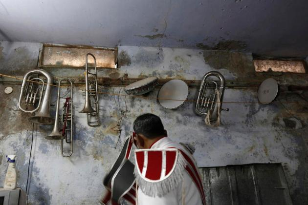 Musical instruments hang on the wall of a basement as a member of a brass band gets ready to perform at the wedding procession in New Delhi