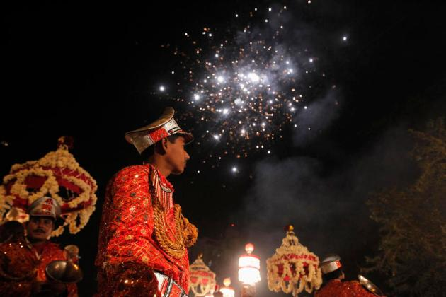 Members of the brass band play as fireworks are set off during a wedding procession in Noida