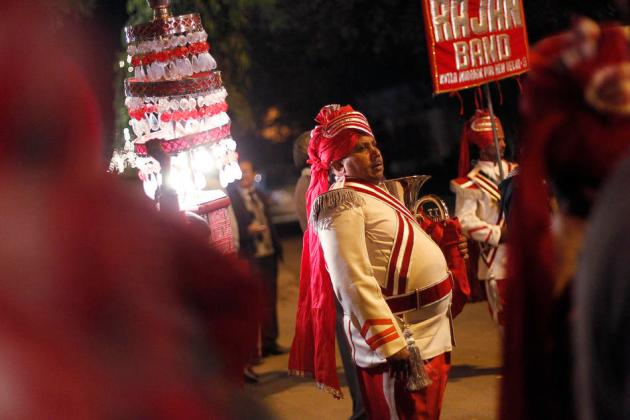 Singh, member of a brass band, pauses as his other members perform during a wedding procession in New Delhi