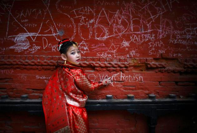 Sona Nakarmi, 7, writes on a wall at the Saraswati temple during the Shreepanchami festival in Kathmandu