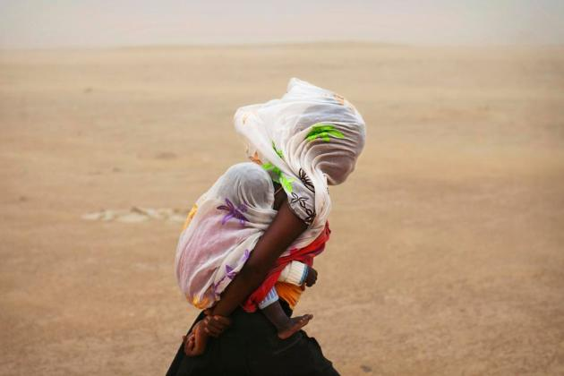 A woman carrying her baby and wrapped with a shawl walks through a sandstorm in Timbuktu