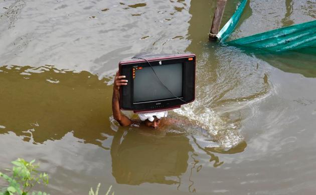 A flood-affected man carries his television set to a safer place in the northern Indian city of Allahabad